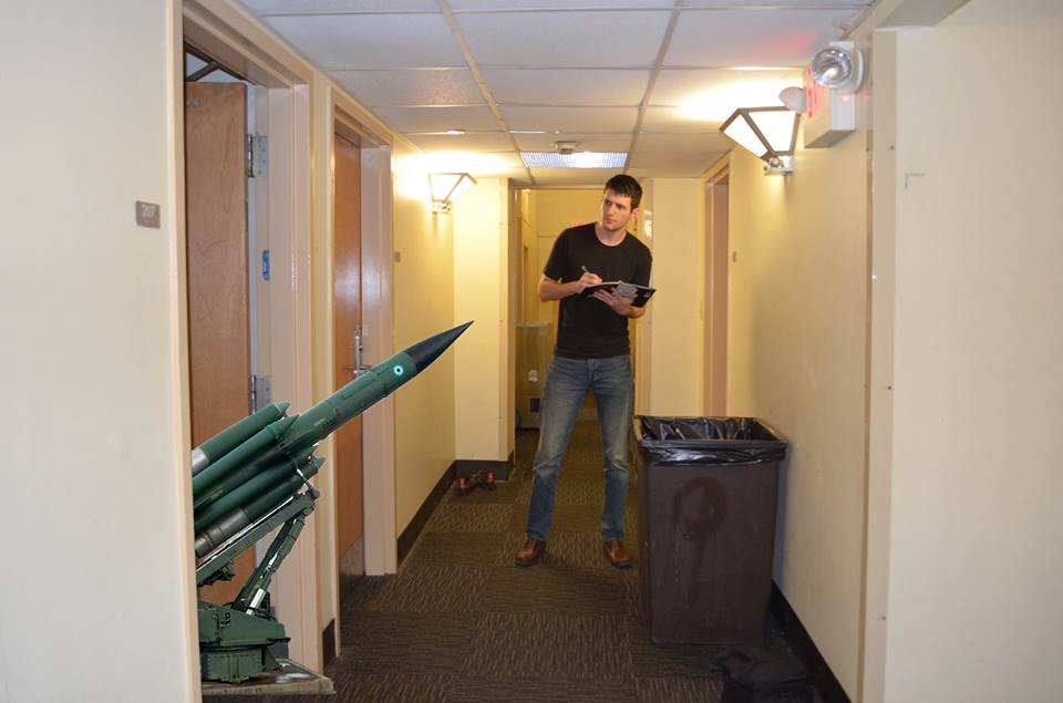 An IFC inspector tacks off another demerit against Chi Phi for anti-aircraft artillery.